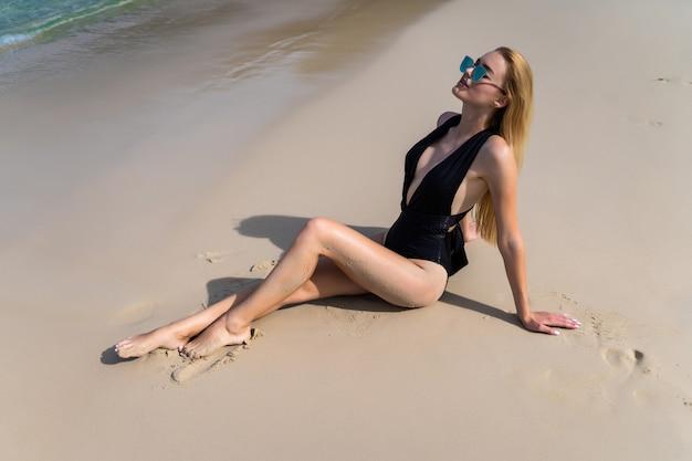 Młoda seksowna blondynki kobieta kłaść na tropikalnej kurort plaży w eleganckim czarnym stroju kąpielowym