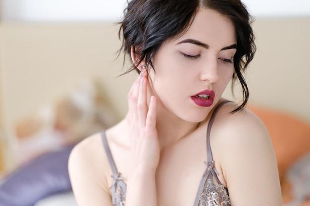 Młoda seksowna brunetka dziewczyna w bieliźnie w jej sypialni