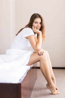 Młoda seksowna dziewczyna w bieliźnie siedzi na łóżku w godzinach porannych