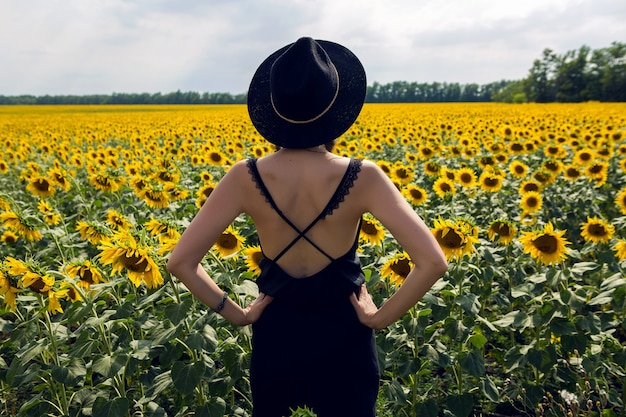 Młoda seksowna dziewczyna w czarnej sukience i kapeluszu w polu z żółtymi słonecznikami
