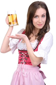 Młoda seksowna dziewczyna w krajowej sukni z szklanym piwem.