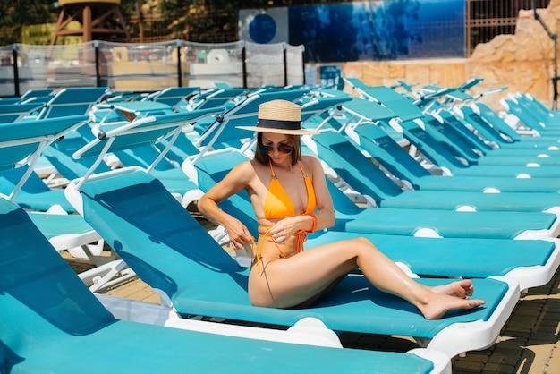 Młoda seksowna dziewczyna w okularach i kapeluszu uśmiecha się szczęśliwie i opala się na leżaku w słoneczny dzień. wesołych wakacji wakacje. wakacje i turystyka.