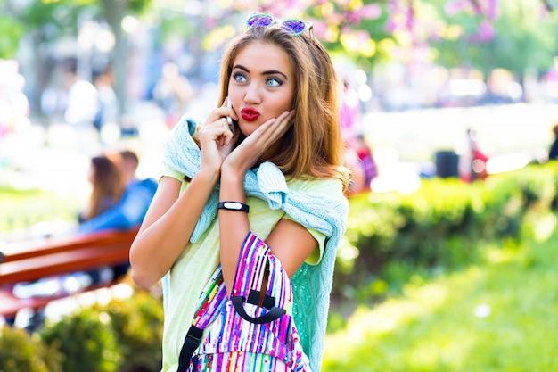 Młoda seksowna elegancka kobieta pozuje na ulicy i rozmawia ze swoim smartfonem z przyjaciółką, nieformalne pastelowe ubrania, słoneczne kolory, wiosna, plener, romantyczne miejsce. zaskoczony