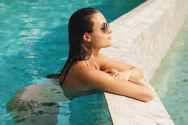 Młoda seksowna kobieta jest relaksująca w basenie