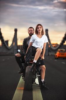 Młoda seksowna kobieta przytulanie ładny mężczyzna w stylowej czarnej skórzanej kurtce, siedząc na motocyklu sportowym na moście w mieście na zachód słońca i całując.