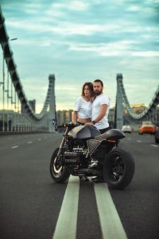 Młoda seksowna kobieta przytulanie słodkiego mężczyzny w stylowej czarnej skórzanej kurtce, siedząc na motocyklu sportowym na moście w mieście o zachodzie słońca i całując
