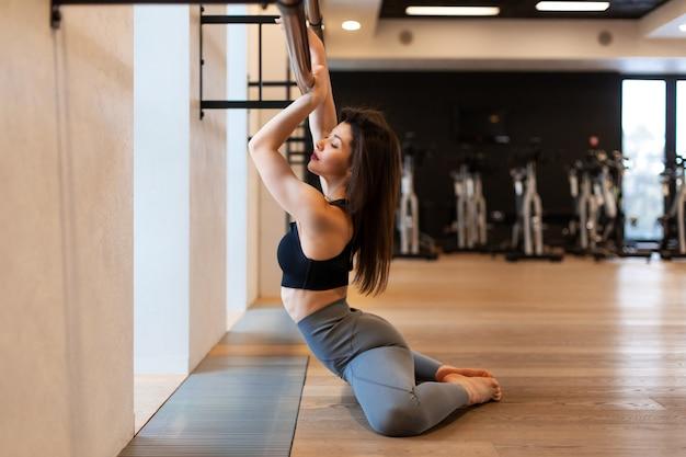 Młoda seksowna kobieta robi rozciągających ćwiczeniom w gym