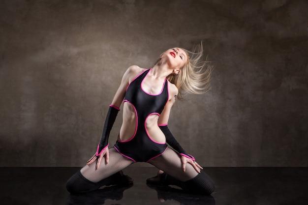 Młoda seksowna kobieta tańczy w studio na szarym tle