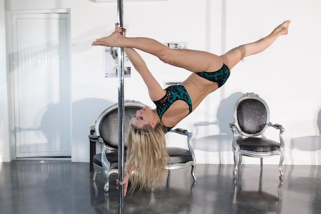 Młoda seksowna kobieta taniec na rurze w centrum fitness