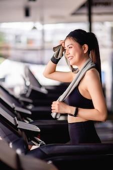Młoda seksowna kobieta ubrana w odzież sportową, tkaninę odporną na pot i smartwatch używa ręcznika wytrzeć pot na czole podczas treningu w nowoczesnej siłowni, uśmiech i patrząc przez okno, kopiować przestrzeń