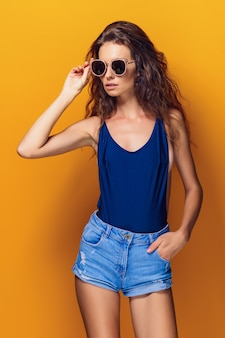 Młoda seksowna kobieta ubrana w strój kąpielowy i niebieskie dżinsy, okulary przeciwsłoneczne pozowanie na żółto.