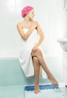 Młoda seksowna kobieta używa balsamu po prysznicu
