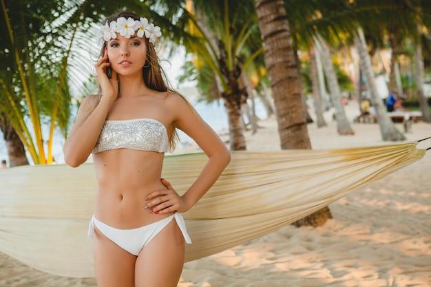 Młoda seksowna kobieta w białym bikini bikini pozowanie na tropikalnej plaży, palmy, hawaje, kwiaty we włosach, zmysłowe, szczupłe ciało, słonecznie, ciesząc się wakacjami, podróżując po wyspie