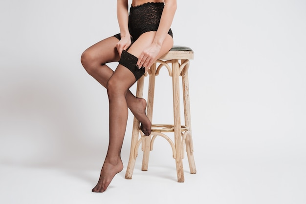 Młoda seksowna kobieta w bieliźnie i pończochach siedzi na krześle na białym tle