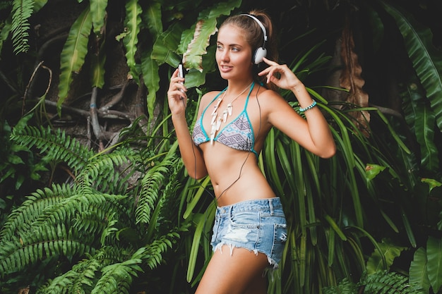 Młoda seksowna kobieta w bikini i dżinsowych szortach, słuchanie muzyki na słuchawkach, trzymanie smartfona, opalona skóra, chude ciało, zielone tropikalne tło, taniec, uśmiech