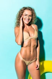 Młoda seksowna kobieta w bikini wewnątrz nadmuchiwanego pierścienia na białym tle na zielonej ścianie