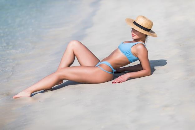 Młoda seksowna kobieta w bikini z słomianym kapeluszem przy tropikalną plażą