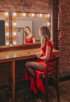 Młoda seksowna kobieta w czerwonej długiej sukni przygotowuje się do strzelania i patrzy na swoje odbicie w lustrze w garderobie