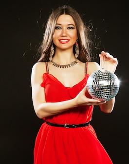 Młoda seksowna kobieta w czerwonej sukience trzymająca disco ball