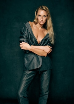 Młoda seksowna kobieta w garniturze na nagim ciele na ciemnym tle