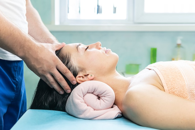 Młoda seksowna kobieta w spa dostaje masaż twarzy i masaż głowy. koncepcja zabiegów masażu spa.