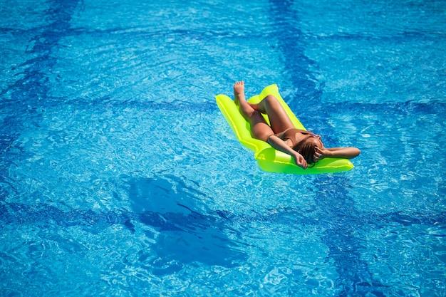 Młoda seksowna kobieta w stroju kąpielowym pływa w basenie na nadmuchiwanym materacu. dziewczyna w okularach przeciwsłonecznych w niebieskim basenie na wakacjach