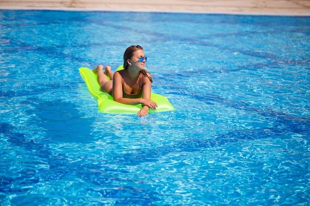 Młoda seksowna kobieta w stroju kąpielowym pływa w basenie na nadmuchiwanym materacu. dziewczyna w okularach przeciwsłonecznych z uśmiechem na twarzach w niebieskim basenie na wakacjach