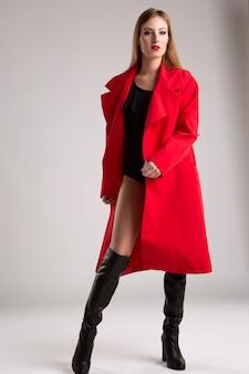 Młoda seksowna modelka z długimi włosami w jaskrawoczerwonym płaszczu przeciwdeszczowym i czarnym body