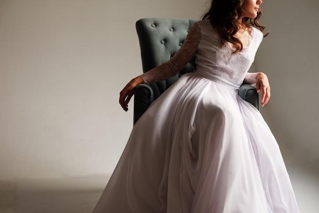 Młoda seksowna panna młoda w wspaniałej sukni w studiu siedzi w wygodnym krześle