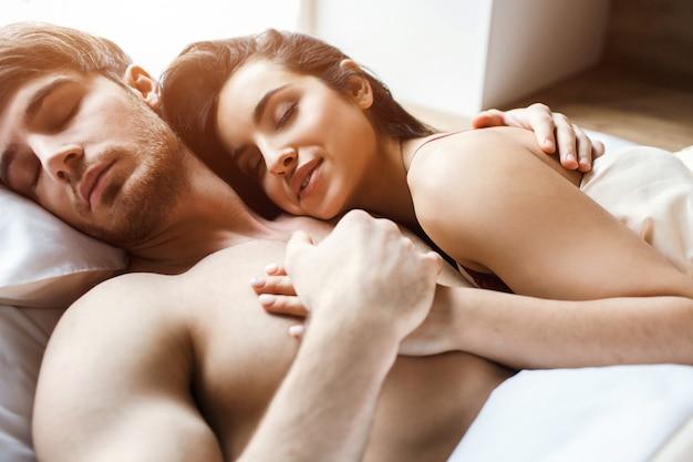 Młoda seksowna para po intymności na łóżku. spać i śnić razem. zadowoleni młodzi ludzie szczęśliwi i zachwyceni. kobieta objąć mężczyznę. trzyma ją za rękę. atrakcyjne modele.