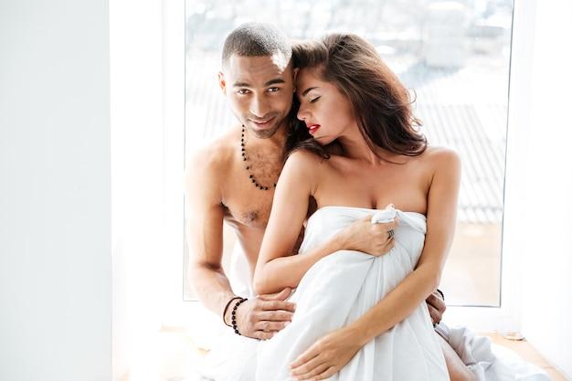 Młoda seksowna para razem stojąca i przytulająca się przy oknie