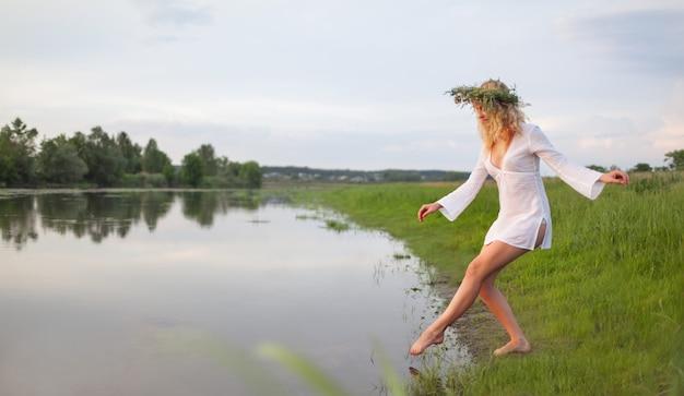 Młoda seksowna piękna blond kobieta w białej mini sukience i wieniec kwiatowy stojąc i próbując wody