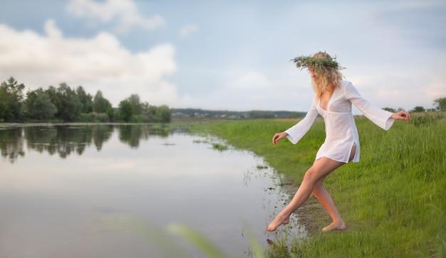Młoda seksowna piękna blond kobieta w białej mini sukni i wieniec kwiatowy stoi i próbuje wody w letni dzień