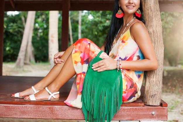 Młoda seksowna piękna kobieta w kolorowej sukience, lato w stylu hippie, tropikalne wakacje, zielona torebka z grzywką, akcesoria, ręce z bliska z bransoletkami, palce, manicure