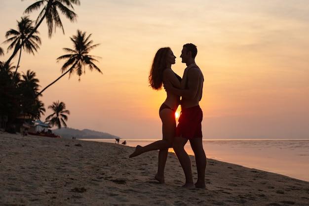 Młoda seksowna romantyczna para zakochana na zachodzie słońca szczęśliwy na plaży latem razem zabawy na sobie kostiumy kąpielowe