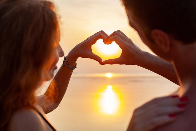 Młoda seksowna romantyczna para zakochanych szczęśliwy na letniej plaży razem dobrze się bawić na sobie kostiumy kąpielowe pokazując znak serca na zachodzie słońca