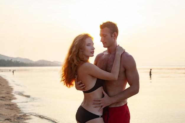 Młoda seksowna romantyczna para zakochanych szczęśliwy na letniej plaży razem zabawy na sobie kostiumy kąpielowe