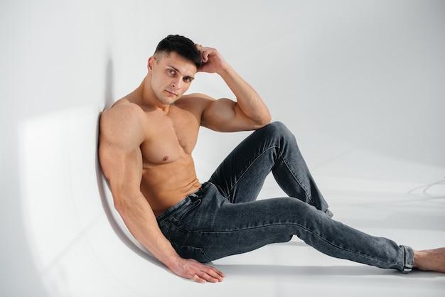 Młoda seksowna sportowiec z doskonałym abs siedzi na podłodze w studio topless w dżinsach w tle. zdrowy styl życia, prawidłowe odżywianie, programy treningowe i odżywianie na odchudzanie.