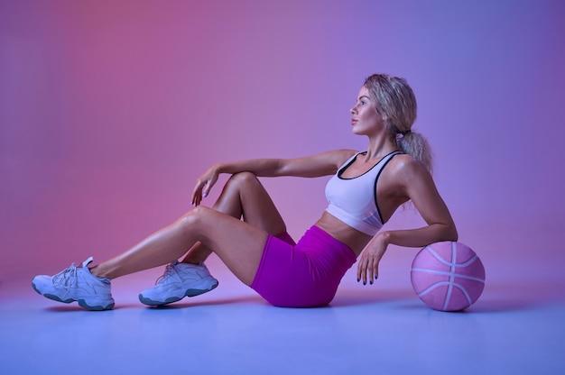 Młoda seksowna sportsmenka z piłką siedzi na podłodze w studio, neonowe tło. fitness kobieta na sesji zdjęciowej, koncepcja sportu, aktywny styl życia