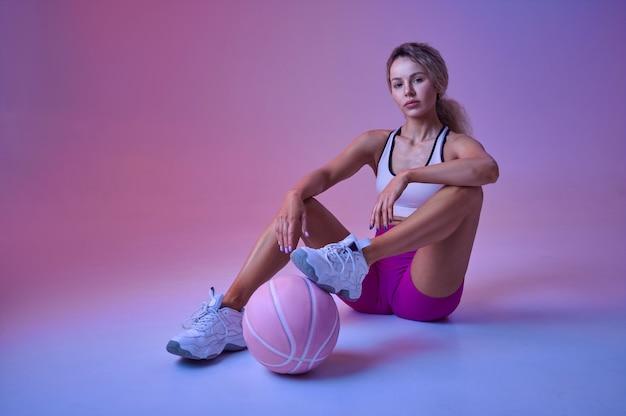 Młoda seksowna sportsmenka z piłką siedzi na podłodze w studio, neonowe tło. fitness kobieta na sesji zdjęciowej, koncepcja sportu, motywacja do aktywnego stylu życia