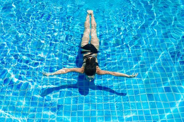 Młoda seksowna szczupła kobieta relaksuje w pływackim basenie z krystaliczną błękitne wody