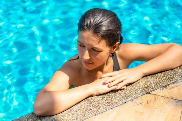 Młoda seksowna szczupła kobieta relaksuje w tropikalnym pływackim basenie z krystaliczną błękitne wody w gorącym letnim dniu