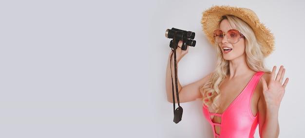 Młoda seksowna uśmiechnięta szczęśliwa blondynka w różowym stroju kąpielowym, słomkowym kapeluszu, okularach przeciwsłonecznych, podekscytowana prezentacją produktu. kobieta na białym tle z palmą zielonymi liśćmi.