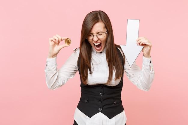 Młoda sfrustrowana kobieta biznesu w okularach krzyczy trzymać bitcoina, strzałka spadku wartości w dół na białym tle na pastelowym różowym tle. szefowa. koncepcja bogactwa kariery osiągnięcia. skopiuj miejsce na reklamę.