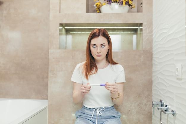 Młoda sfrustrowana kobieta patrząca na szybki pozytywny lub negatywny wynik testu ciążowego