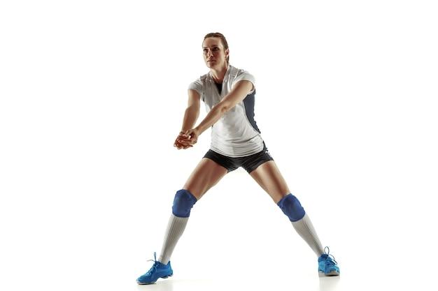 Młoda siatkarka na białym tle na tle białego studia. kobieta w sportowym sprzęcie i butach lub tenisówkach, trening i ćwiczenia. pojęcie sportu, zdrowego stylu życia, ruchu i ruchu.
