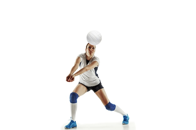 Młoda siatkarka na białym tle na tle białego studia. kobieta w sportowym sprzęcie i butach lub trampkach, trenuje i ćwiczy. pojęcie sportu, zdrowego stylu życia, ruchu i ruchu.