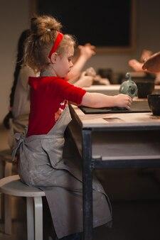 Młoda siedmioletnia dziewczyna w warsztacie garncarskim, tworząc miskę z gliny. warsztaty garncarskie dla dzieci.