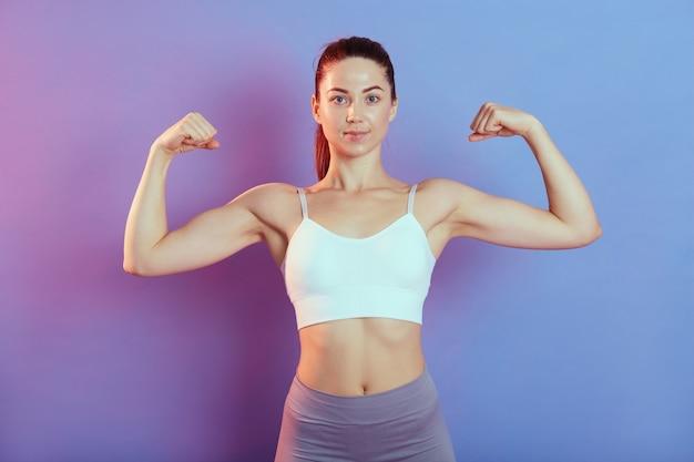 Młoda silna kobieta patrząc prosto w kamerę, podnosząca obie ręce i pokazująca bicepsy, ubrana w bluzkę i legginsy, odizolowana na kolorowym tle, dama z idealną sylwetką i kucykiem.