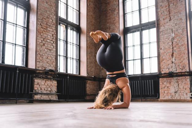Młoda silna kobieta wykonuje kompleks rozciągających asan jogi w klasie stylu loft. stanowisko shirshasana. stanie na rękach.